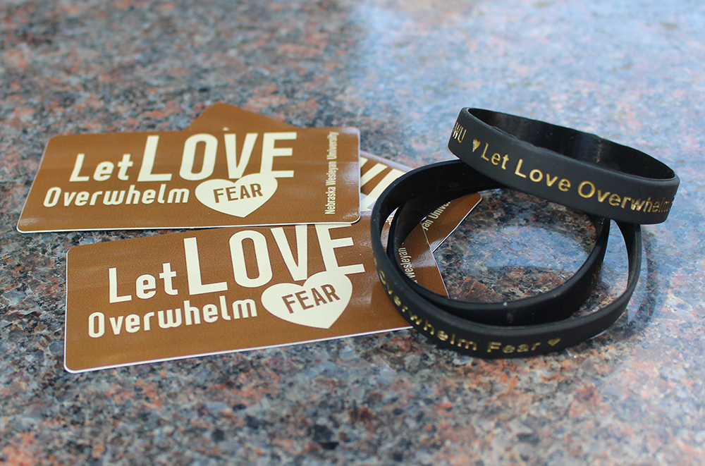 Picture of 'Let Love Overwhelm Fear' stickers and bracelets.