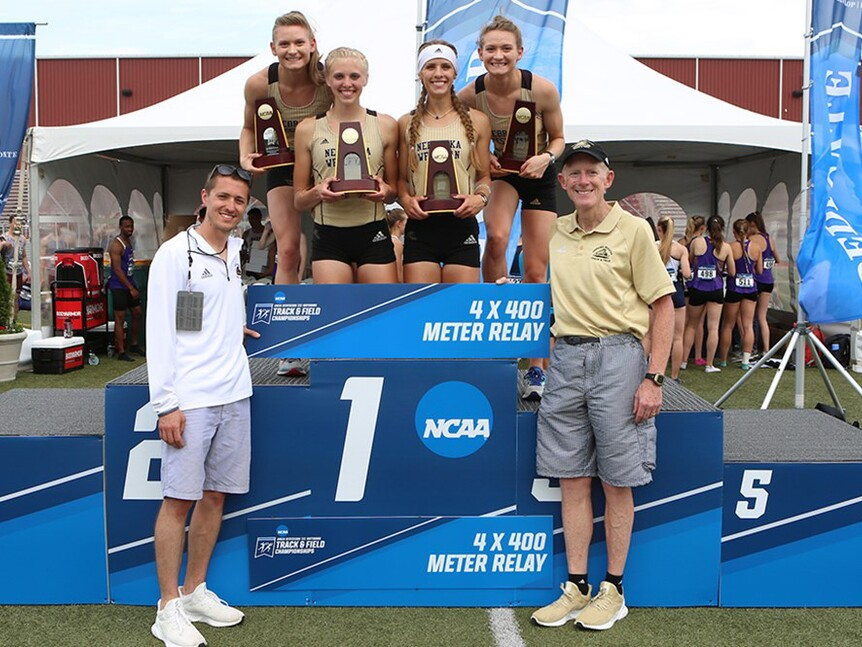NWU's women 4x400 relay team on the top podium of winners flanked by their coaches.