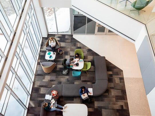 From a third floor view looking down on students studying in the entrance of Acklie Hall of Science.
