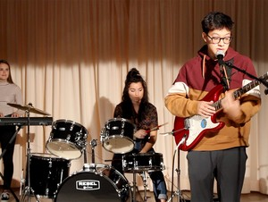 A student playing guitar, a student playing the drums and a student at playing a keyboard.