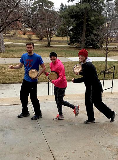 Three people pretending to run holding pies.